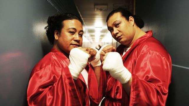 Zwei geschminkte samoanische Boxer in rotem Satinboxmantel posieren in Boxhaltung.