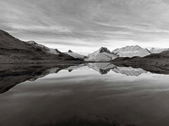 Schwarzweissbild: In einem klaren Bergsee spiegelt sich eine Gebirgskette.
