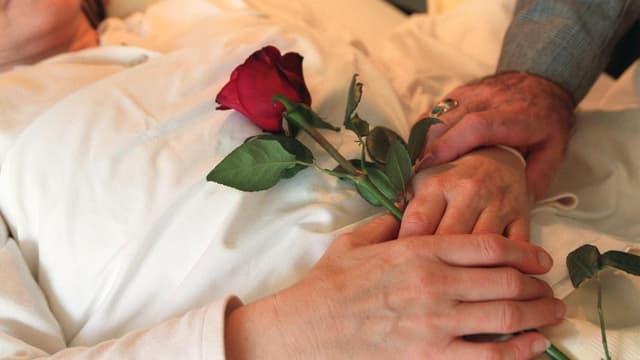 Eine Frau liegt in einem Bett und hälte eine rote Rose auf ihrem Bauch - zusammen mit Männerhänden.