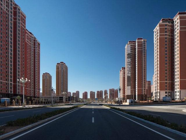 Eine menschenleere Strasse, gesäumt von Hochhäusern.