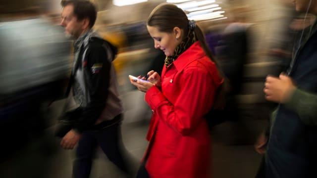 Eine Frau schaut beim Gehen auf ihr Smartphone.