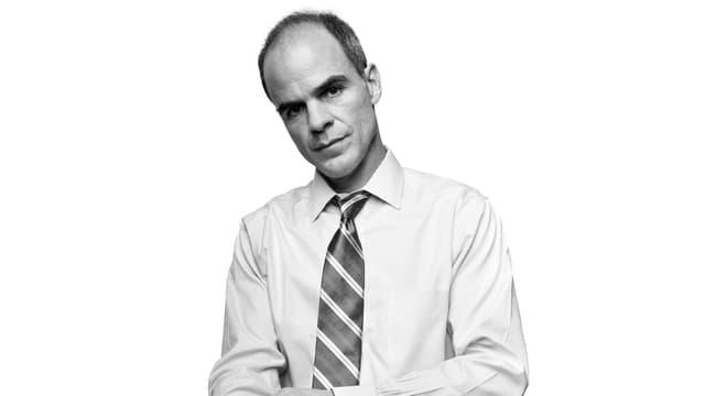 Ein kahlköpfiger Mann in Hemd und Krawatte.