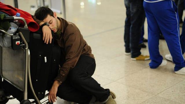 Ein Mann sitzt auf einem Gepäckwagen und schläft.