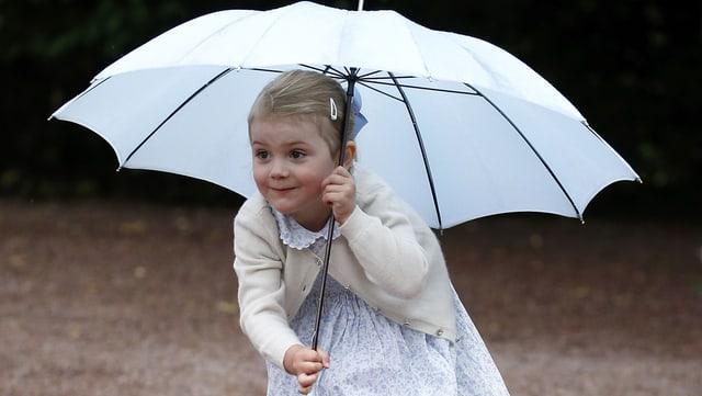 Ein kleines Mädchen im blauen Kleid versteckt sich unter einem hellblauen Regenschirm.