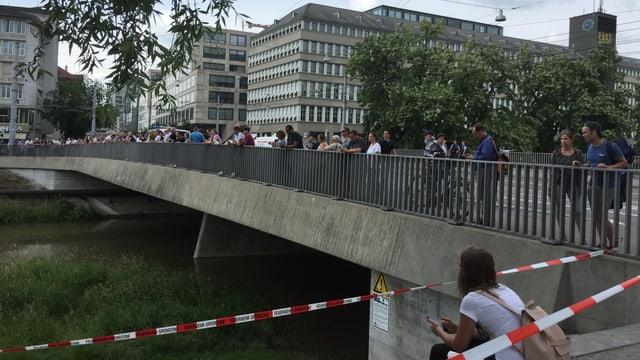 Schaulustige auf einer Brücke schauen auf den Fluss.
