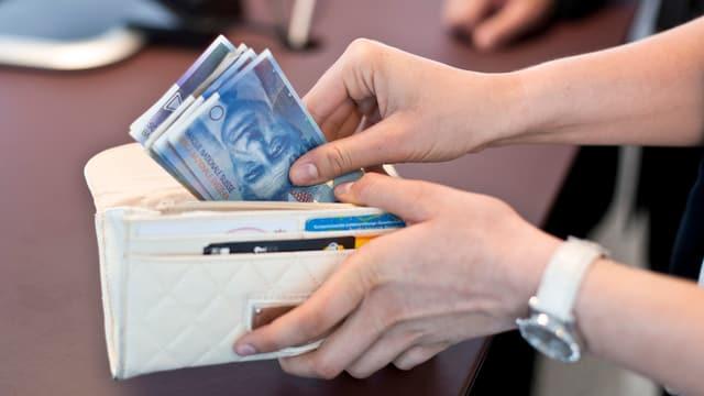 Eine Kunden hebt von der Bank Geld ab und steckt es in ihr Portemonnaie.