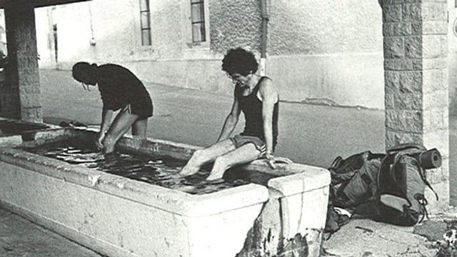 Kurt Saurer und Daniel Bähler tauchen ihre Füsse in einen Brunnen ein.