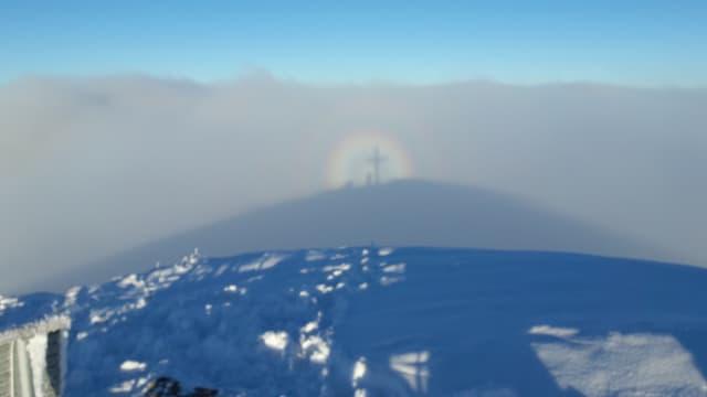 Im Nebelschatten ist ein Mann neben einem Gipfelkreuz zu erkennen. Um den Kopf des Schattens hat sin eine Glorie gebildet.