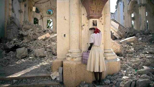 Ina dunna ura en las ruinas d'ina catedrala a Haiti.