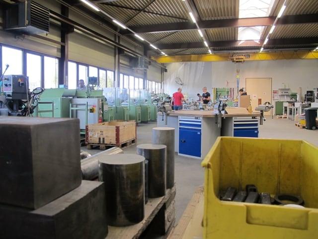 Blick in die Montagehalle mit Eisenabfall und verschiedenen Maschinen.