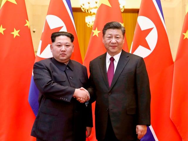 Kim und Xi geben sich die Hand.