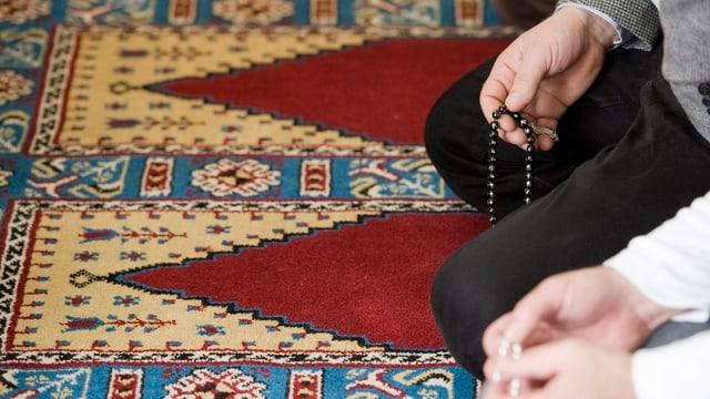 Bild von den Händen zweier knienden Muslime beim Gebet.