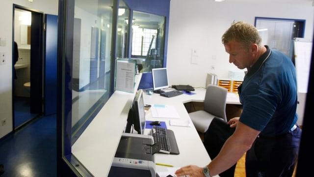 Mann in verglastem Überwachungsraum