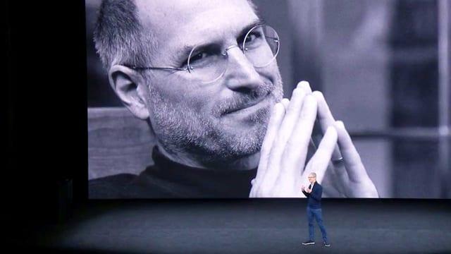 Eine Nahaufnahme von Steve Jobs wird auf eine grosse Wand projiziert. Davor steht ein Mann in Jeans und hält eine Präsentation.