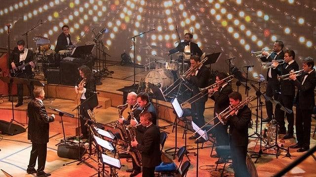 Ein Orchester auf einer festlichen Bühne.
