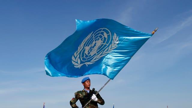 Ein Blauhelm-Soldat trägt die UNO-Flagge