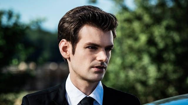 Stalder als Fabio Testi im Anzug und mit gegelten Haaren.