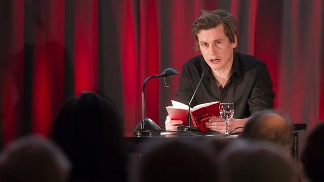 Ein mann liest vor Publikum aus einem Buch