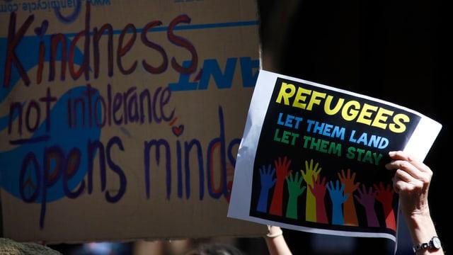 """An einer Demo hält jemand ein Schild in die Höhe, darauf steht """"Refugee, let them land, let them stay""""."""