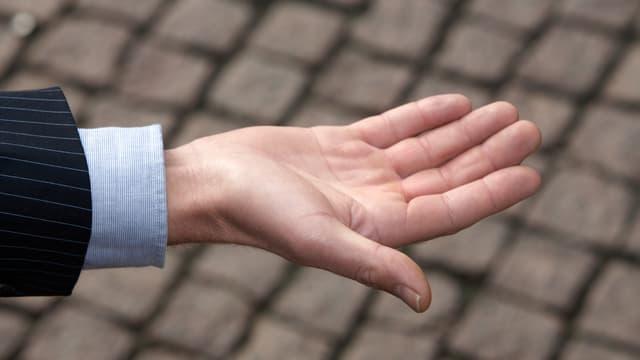 Männliche offene Hand mit Anzug und Hemd.