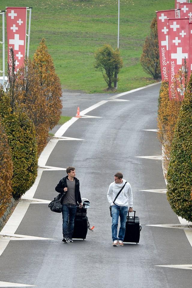 Valentin Stocker und Fabian Frei ziehen ihre Rollkoffer über eine Landstrasse in Feusisberg.