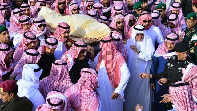 Leichnam auf einer Bahre. Leute tragen ihn durch Menschenmassen.