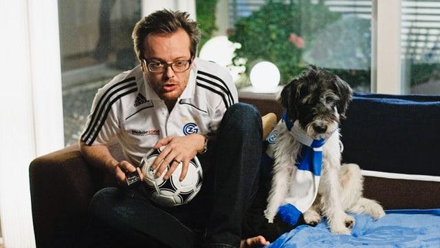 Ivo und Hund Fredy sitzen auf dem Sofa. Ivo hält einen Fussball in den Händen und Fredy trägt einen Schal.