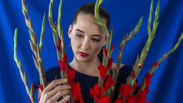 Eine junge Frau vor blauem Hintergrund hält einen Strauss rot leuchtender Orchideen