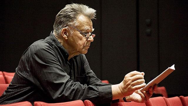 Peter Gülke sitzt im Zuschauerraum eines Konzertsaals und liest.