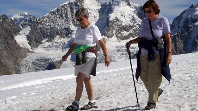 Zwei ältere Frauen auf Schnee gehend