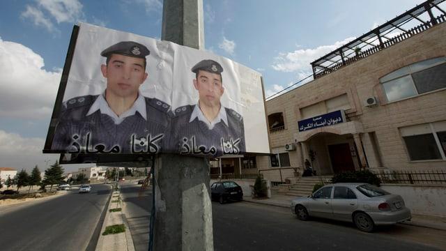 Ein Doppelplakat mit dem Gesicht des entführten jordanischen Piloten in einer Strasse in Ammann.