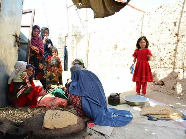 Shekiba (vorne Mitte) backt vor ihrer Hütte afghanisches Fladenbrot für die Familie.