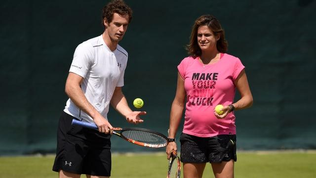 Andy Murray im Tennisoutfit mit weissem Polo-Shirt hält einen Tennisschläger während seine Trainerin im pinken T-Shirt Anweisungen gibt.