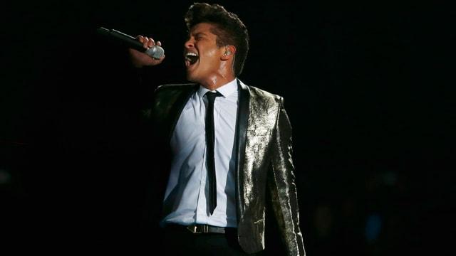 Bruno Mars im weissen Hemd mit Silberanzug auf der Bühne am Singen.
