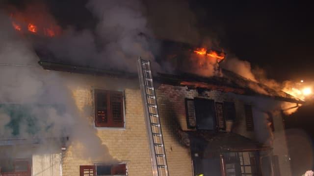 Ein Haus mit gelber Fassade brennt, Rauch dringt aus den Fenstern, eine Leiter steht an der Hauswand.