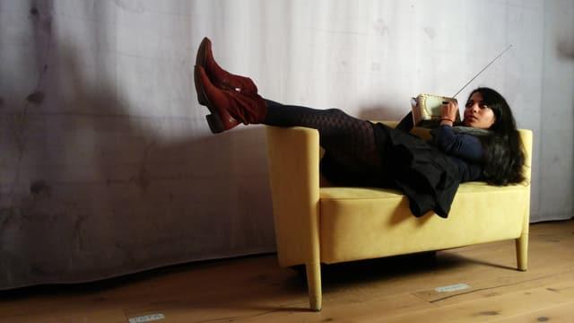 Reena liegt mit Retroradio in der Hand auf einem gelben Sofa