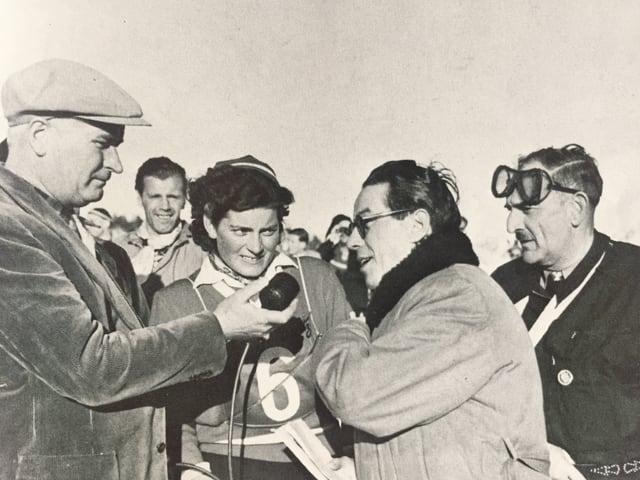 Schwarz-weiss Foto mit vier Menschen und einem Radiomikrofon