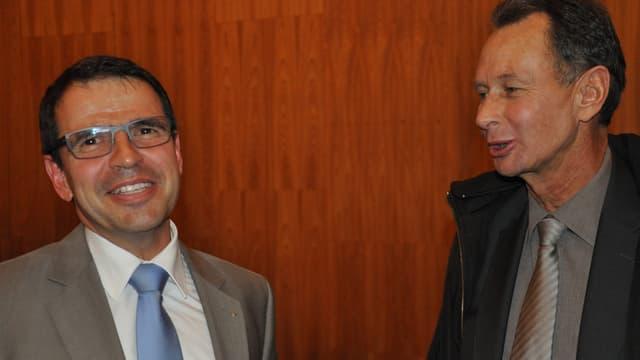 Matthias Jauslin nimmt strahlend die Gratulationen von Phillip Müller entgegen. Beide tragen eine Kravatte.