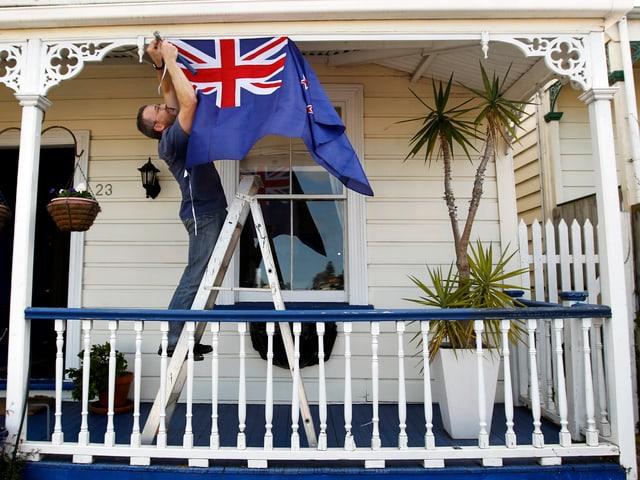 Ein Rugy-Fan hängt vor seinem Hauseingang die Flagge Neuseelands auf.
