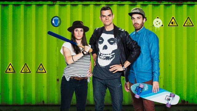 Bettina mit Baseballschläger über der Schulter, Robin, Matthias mit Skateboard vor Schiffscontainer