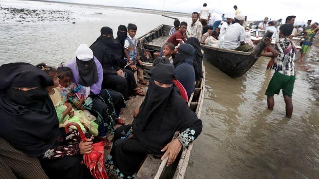 Boote mit Frauen im Tschador und Kindern auf einem Fluss.