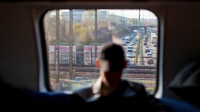 Blick aus einem Zugfenster auf einen Stau auf der Autobahn