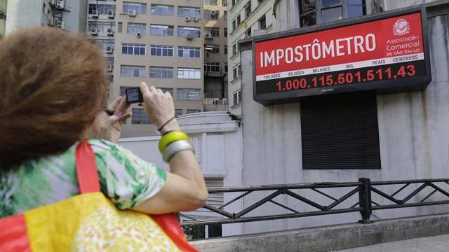 Eine Frau macht ein Foto der Schuldenuhr, einer Digitalanzeige an einer Aussenwand.