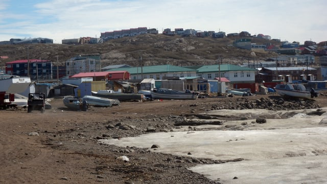 Boote liegen auf erdigem Boden vor einer kleinen Stadt mit flachen Häusern.