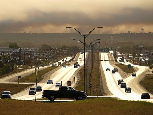 Blick über einen Highway. Die Strassen scheinen zu glühen. Über dem Horizont türmen sich Rauchwolken.