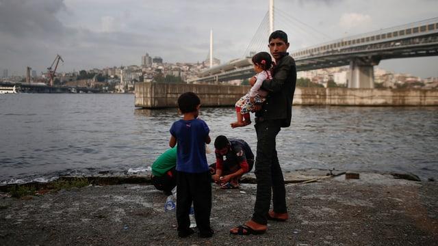 Ein syrischer Flüchtling steht mit seinen Kindern vor einer Brücke in Istanbul