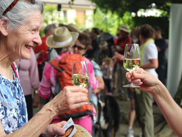 Zwei Frauen stossen mit einem Glas Wein auf das Erreichen des Ziels an.