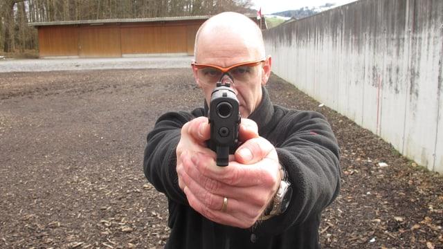 Ein Polizist in zivil zielt mit einer Waffe direkt in die Kamera.