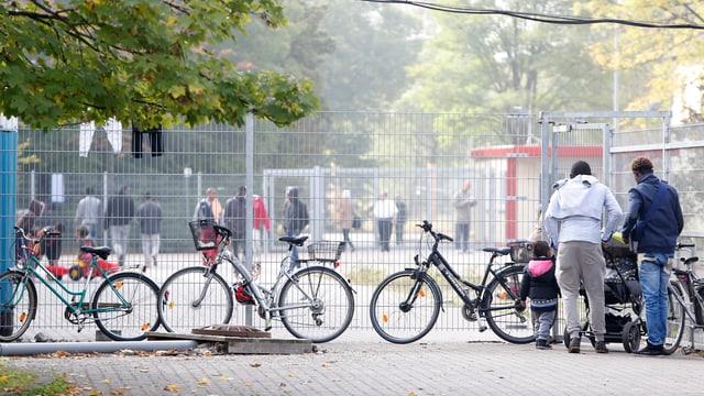 Menschen stehen vor und hinter einem Gitterzaun, der das Gelände umschliesst.