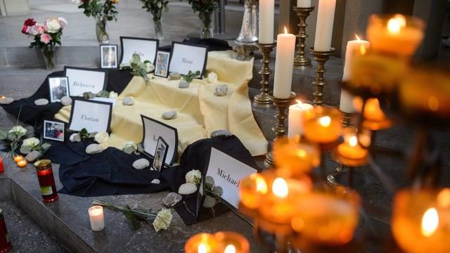 Kerzen und Gedenktafeln auf dem Boden.
